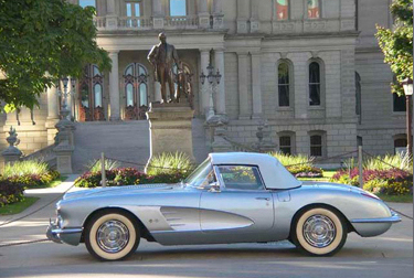 Picture of Patrick and Ellie's 1958 silver/blue Corvette in front of the State Capitol.